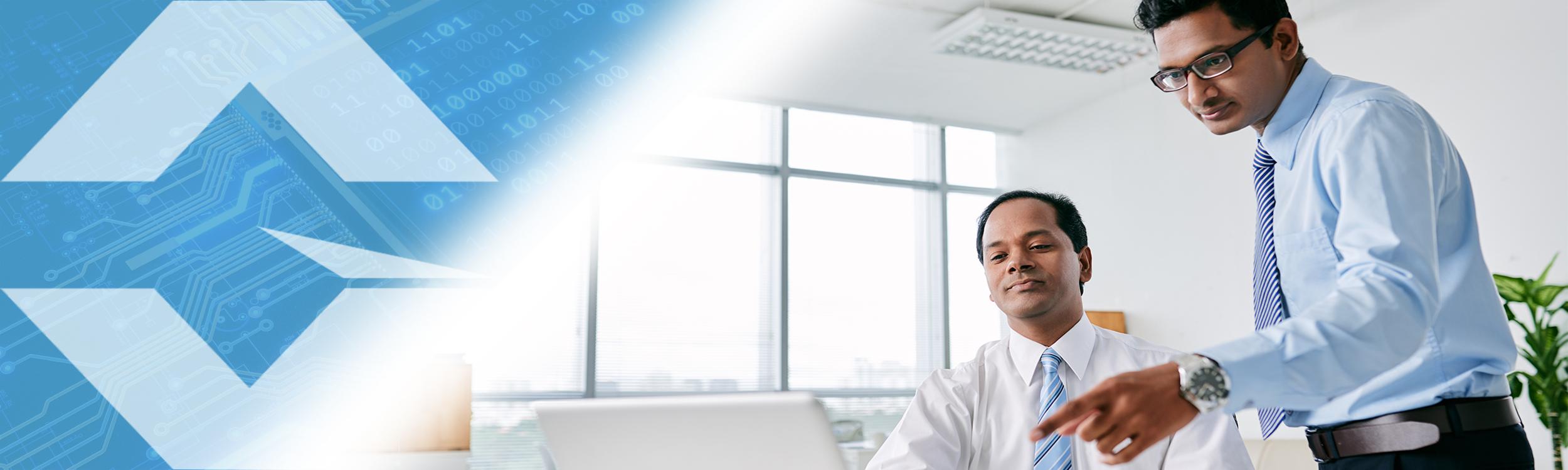 Gloresoft, Recruiting indische IT-Spezialisten; zwei indische Männer im Büro. Einer steht und zeigt dem anderen etwas auf dem Computerbildschirm.